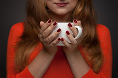 Woman holding hot cup and smiles Royalty Free Stock Image