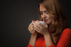 Woman holding hot cup and smiles Royalty Free Stock Photo