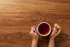 Woman holding hot cup of tea with cookies Stock Photo