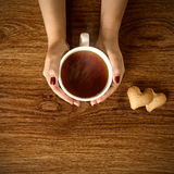 Woman holding hot cup of tea with cookies on wooden table Royalty Free Stock Photo