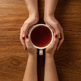 Woman holding hot cup of tea with cookies on wooden table Royalty Free Stock Photos