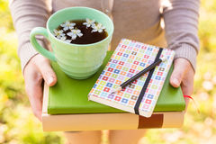 Woman holding hot cup of tea with notebook and pencil Stock Images