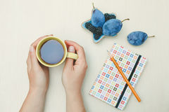 Woman holding hot cup of tea with notebook and pencil Stock Photography