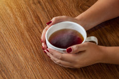 Woman holding hot cup of tea stock image
