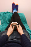 Woman holding a hot drink, relaxing with her feet up Stock Photo