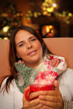 Woman holding Hot Drink seating near Christmas Tree and Fireplace Stock Photos