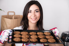 Woman holding hot roasting pan with cookies. Beautiful woman holding hot roasting pan with oat cookies Royalty Free Stock Photo