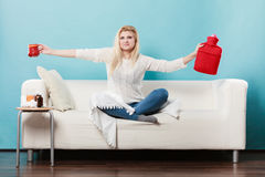 Woman holding hot water bottle and tea in cup Royalty Free Stock Images