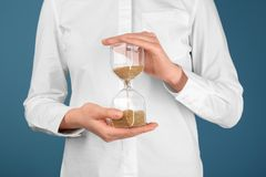 Woman holding hourglass on color background. Time management concept royalty free stock photo
