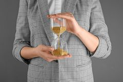 Woman holding hourglass on grey background. Time management concept royalty free stock image