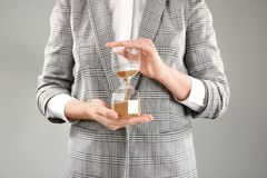 Woman holding hourglass on grey background. Time management concept stock photography