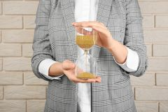Woman holding hourglass near brick wall. Time management concept royalty free stock image