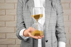 Woman holding hourglass near brick wall. Time management concept royalty free stock photography