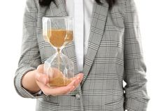 Woman holding hourglass on white background. Time management concept stock photo
