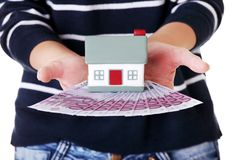 Woman holding a house model and euro bills.  Stock Photos
