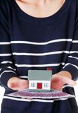 Woman holding a house model and euro bills.  Stock Photo