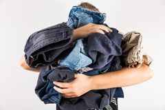 Woman holding huge pile of dirty clothes royalty free stock photo