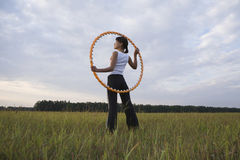 Woman Holding Hula Hoop On Field Stock Photography