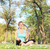 Woman holding a hula hoop seated in meadow Stock Image