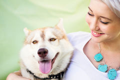 Woman Holding a Husky. A youthful woman is smiling as she holds a young adult dog. The dog is a Siberian Husky/Alaskan Malamute of red and white colouring. They royalty free stock photos