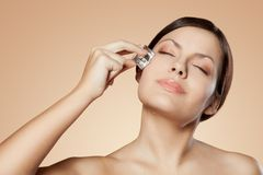 Woman holding ice cube on her face Stock Photography