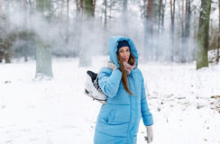 Woman holding ice skates outdoors in snow. Royalty Free Stock Photos