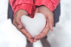 Woman holding icy snow heart. In hands Royalty Free Stock Photography