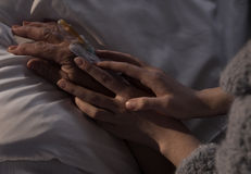 Woman holding ill mother hand Stock Images