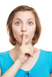 Woman holding index finger in front. Young woman holding her index finger in front of her mouth Stock Photos