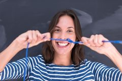 Woman holding a internet cable in front of chalk drawing board Royalty Free Stock Photo