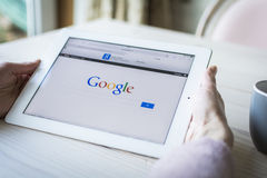 Woman holding iPad showing google search page. Close up of google search showing on iPad or tablet pc. Google search screen. Vintage style Stock Photo