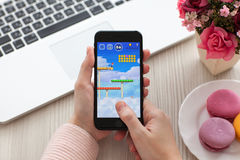 Woman holding iPhone 7 Jet Black game Super Mario Run Royalty Free Stock Photos