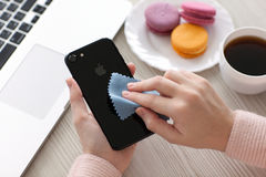 Woman holding iPhone 7 Jet Black Onyx and cleaning it Stock Photo