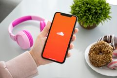 Woman holding iPhone X with music service SoundCloud royalty free stock photo