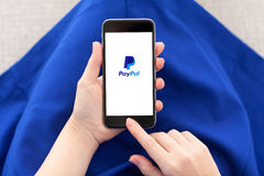 Woman holding iPhone 6 with PayPal on the screen Royalty Free Stock Images
