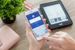 Woman holding iPhone 6S Rose Gold with Facebook on screen Stock Photography