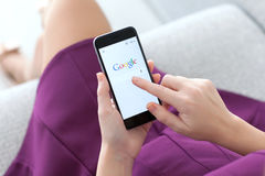 Woman holding iPhone 6 with service Google on the screen Stock Image