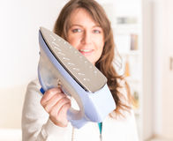 Woman holding iron Stock Photography