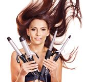 Woman holding iron curling hair. royalty free stock image