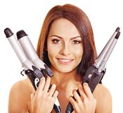 Woman holding iron curling hair. Royalty Free Stock Images
