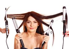 Woman holding iron curling hair. Royalty Free Stock Photography