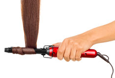 Woman holding iron curling hair. Stock Photography