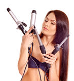Woman holding iron curling hair Royalty Free Stock Photos