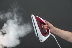 Woman holding an iron with steam on background Royalty Free Stock Images
