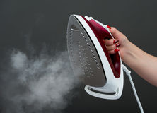 Woman holding an iron with steam on background Stock Image
