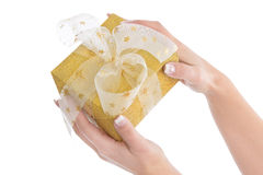 Woman is holding a isolated golden christmas present Stock Photo