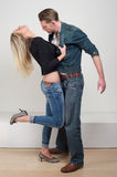 Woman holding jacket of attractive male model in passionate pose Royalty Free Stock Images