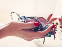 Woman holding jewelry in front of the mirror stock photo