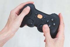 A woman is holding a joystick. Gamepad in hands on a white background Royalty Free Stock Photography