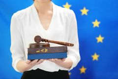 Woman holding judge gavel and law books. On European Union flag background Royalty Free Stock Image
